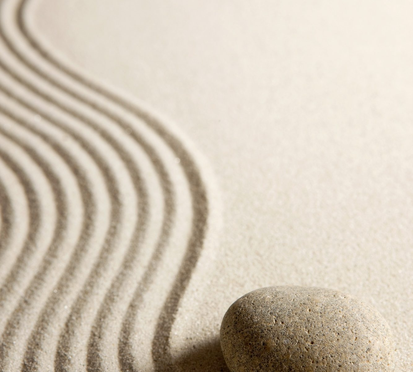 Zen stone beside a river of raked sand