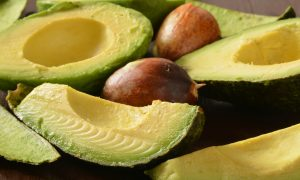 Slices of fresh ripe avocado on a dark wooden table