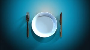 Empty plate with knife and fork against blue background