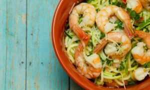 Bowl of Shrimp with Spiralized zucchini on wood board